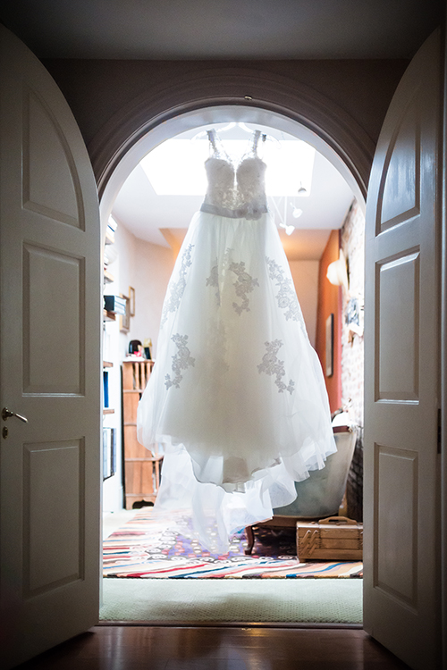 Wedding still life of the dress hanging in an arched doorway