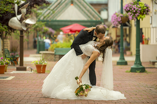 Wedding photograph of a groom dipping and kissing a bride in a b