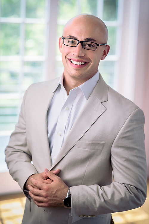 Professional headshot of a young real estate developer